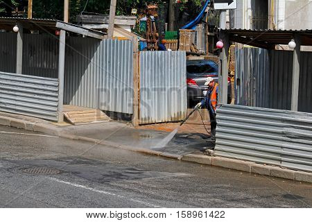 Moscow Russia - July 07 2015: Worker cleaning driveway with high pressure washer in Moscow
