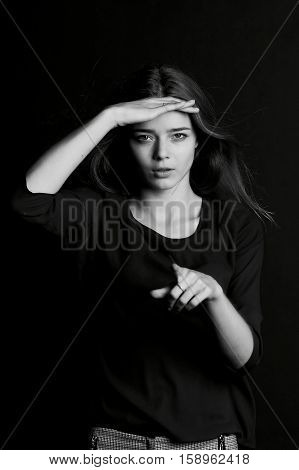 Young beautiful girl with long hair. Gesture I see . BW