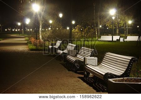 White benches and streetlamp in the park night time. Vignette version with glows.