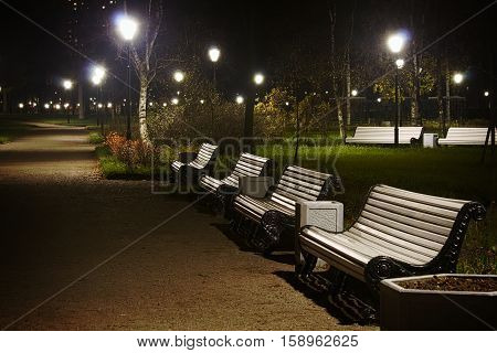 White benches and streetlamp in the park night time. Vignette version.