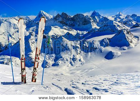 Ski equipment with amazing view of swiss famous mountains in beautiful winter snow. The matterhorn and the Dent d'Herens. In the background Castor and Pollux.