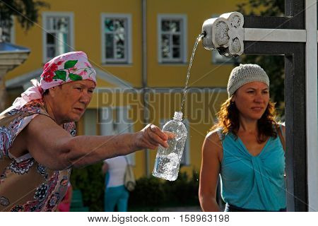 Sergiev Posad Moscow Region Russia - August 11 2015: People collect the holy water in bottle in the Trinity Sergius Lavra in Sergiev Posad