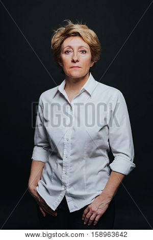 Half length portrait of middle aged woman posing in casual outfit isolated on black background.