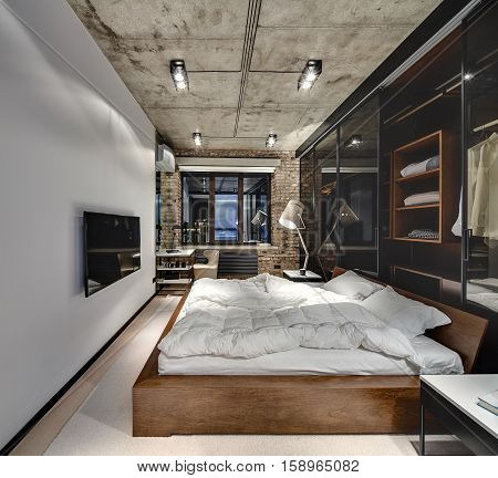 Bedroom in a loft style with brick wall and concrete ceiling. There is a TV, bed with pillows, lamps with lampshades, wardrobe with glass sliding doors, tables, armchair, parquet with a carpet.
