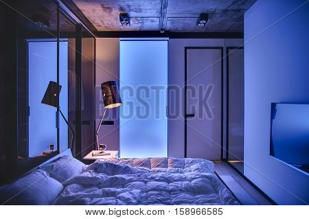 Low light bedroom in a loft style with light walls and concrete ceiling. There is a bed with pillows and blankets, table with book and clock, glowing lamp, TV. Light seeps through frosted glass door.