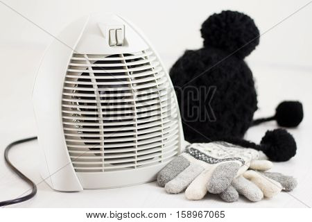 Electric fan heater warming room in winter, gloves and wool hat on white floor isolated