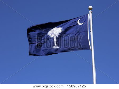 The state flag of South Carolina with it's fingernail moon and stately palm tree on a field of blue waves in the breeze of a spring day.