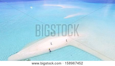 We are standing on a Maldives Island Indian Ocean sandbank, jet ski wake boarding at the background, aerial top view. Turquoise water white sandy beach. Travel summer holiday drone selfie concept