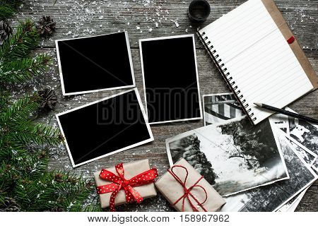blank vintage photo frames on christmas wooden background with gift boxes fir tree notebook and stack of retro pictures. top view