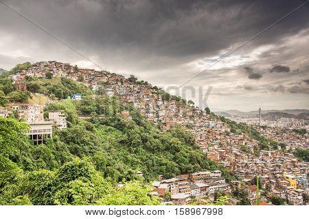 View of Rio de Janeiro Slum, favela Morro dos Prazeres on mountains with dark grey sky, Brazil