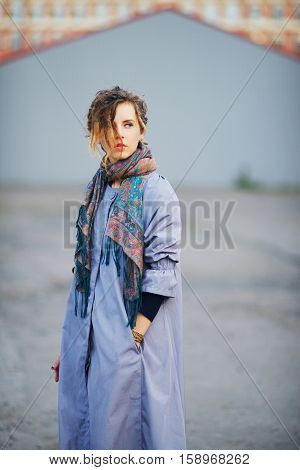 Young beautiful girl in a lavender cloak with a tippet about the neck on a walk around the city