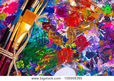 oil paints and paint brushes on a palette. A bunch of brushes on a palette