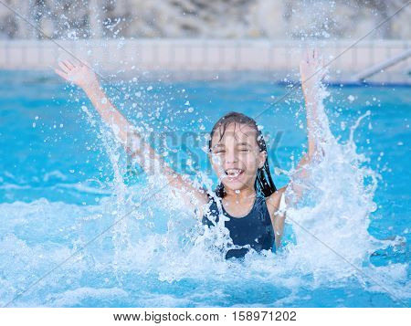 Happy girl jumping in the swimming pool at aquapark. Cute child having fun enjoyable time on vacation. She laughing and splashing water.
