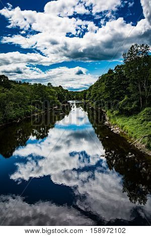 Piscataquis River in Sangerville, Maine shows off its summertime beauty complete with puffy cumulus clouds reflecting off the water.