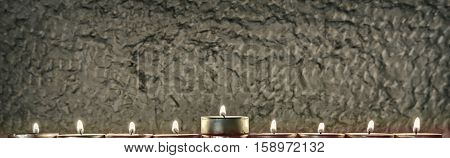Menorah with the glitter lights of candles and stone background