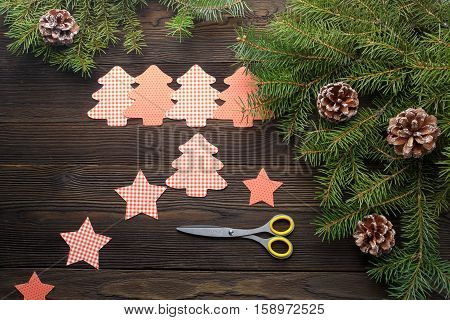 Christmas composition on wooden background with Christmas tree, pine cones, cardboard figures. Cardboard Christmas tree, stars and scissors. Cardboard Christmas figure on a wooden background