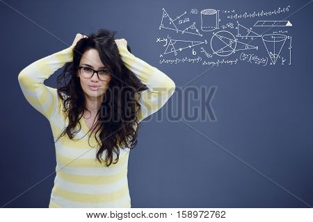 Young amazed woman on blue gray background with math icons. Confusion.