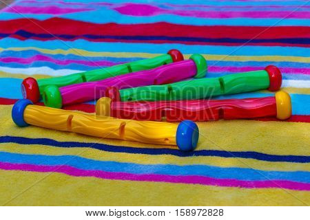 Colourful swimming pool sinking toys to dive out of water on a striped towel