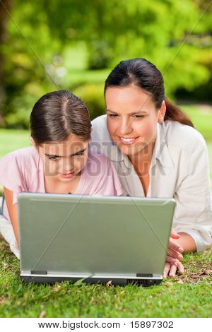 Mother and her daughter looking at their laptop