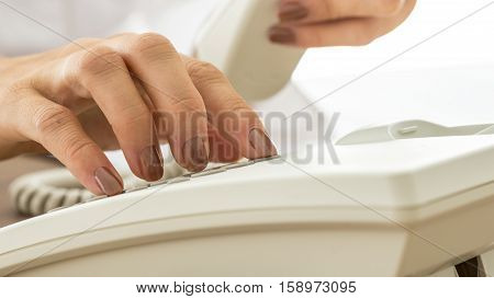 Woman with varnished nails dialling on a land line telephone instrument in a close up view conceptual of business and communication.
