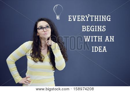 Young thinkful woman on blue gray background with idea sign. Confusion. Predicament. Financial and business concept.