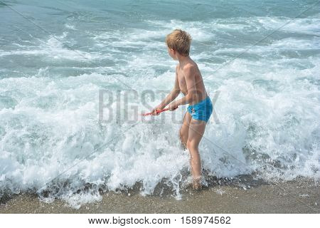 Small blond boy with blue swimming trunks stands with a fishing-net directly in the sea - wave
