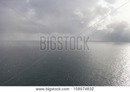 Snowfall over the sea in winter time snowflakes flying over water surface in subtropics cloudy sky and sunlight
