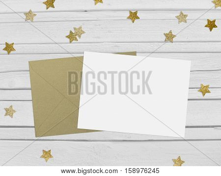 Christmas New Year party mockup scene with golden star shape glittering confetti and blank paper and envelope. White wooden background. Top view.