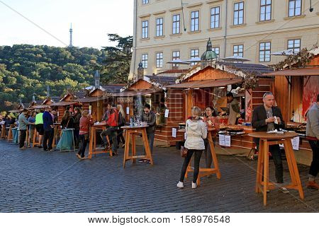 PRAGUE, CZECH REPUBLIC - SEPTEMBER 28, 2015: Local people and tourists eating near wooden stalls with traditional street food in Prague Castle (Hradchany), Prague, Czech Republic.