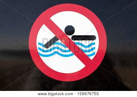 No Swimming sign over black shinny background