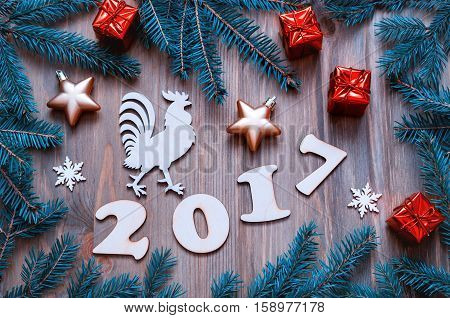 Happy New Year 2017 background with 2017 figures,Christmas toys, blue fir branches and rooster- New Year 2017 symbol.Concept of Happy New Year 2017 holiday- New year of red rooster. Flat lay, top view