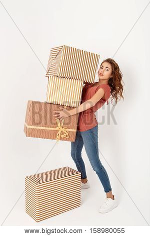 Young beautiful girl carrying big gift boxes Isolated Copy space