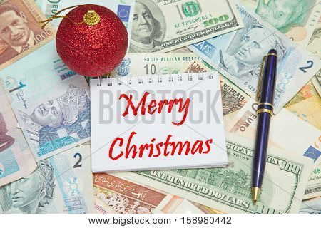 Notebook page with text MERRY CHRISTMAS background from different world Currencies