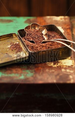 grated dark chocolate in vintage tin on wooden background