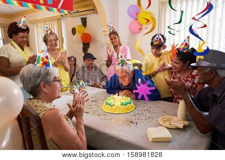 Group of old friends and family celebrating senior man 80 birthday party in retirement home. Happy elderly people having fun. Grandfather blowing candles on cake. poster