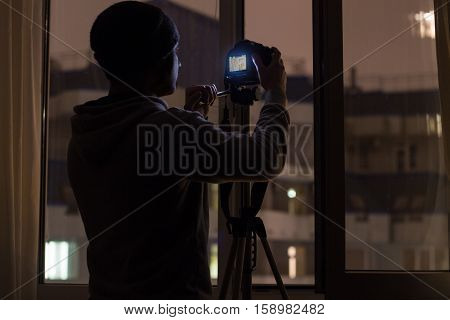 hidden paparazzi is shooting target from window across the street at night