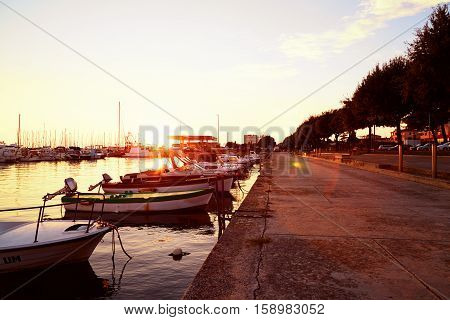 Beautiful quay near the sea on sunset. Ships yachts and catters moored to the pier.