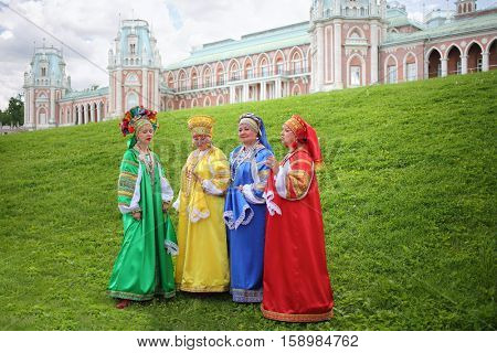 MOSCOW - JUN 06, 2015: Four women in colorful Russian folk costumes sing on the green lawn in front of the manor at the festival of fire and rescue service in Tsaritsyno