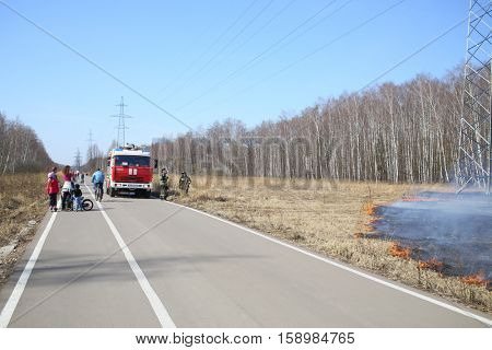 MOSCOW - APR 12, 2015: Fire truck and firefighters near burning dry grass along the birch grove in the spring