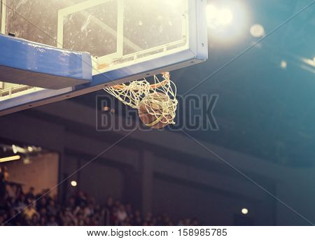 Ball in hoop at basketball game