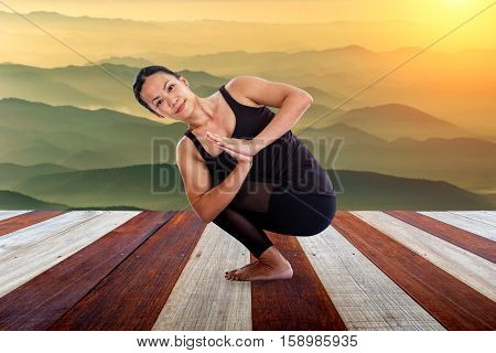 Asian woman doing yoga fitness exercise outdoor in beautiful mountains landscape at morning sunrise Namaste Lotus pose.
