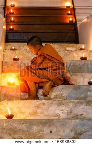 Portrait young novice monk sitting in the staircase at old temple and many candle background Ayutthaya Province Thailand