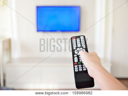 Hand holding tv remote control and surfing programs on television. Teenage girl watching TV in the living room or bedroom. copy space.