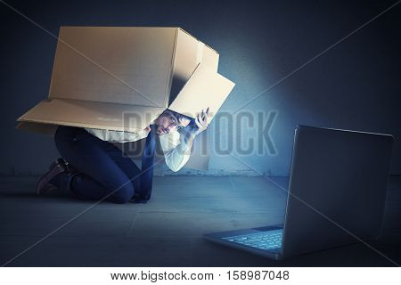 Afraid businessman hidden inside a cardboard businessman looks his laptop. Bullying on the web concept