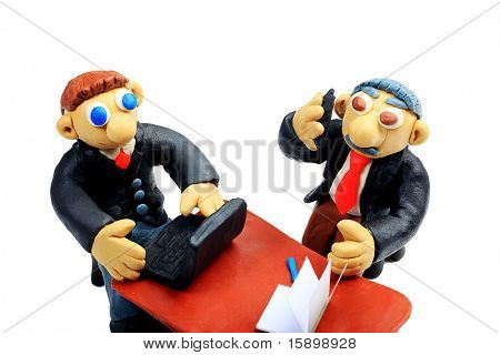 Shot of two plasticine businessmen working at the office. Isolated over white background.