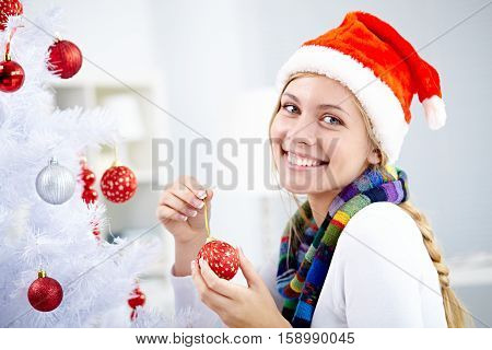 Young beautiful woman decorating her Christmas tree and smiling at camera