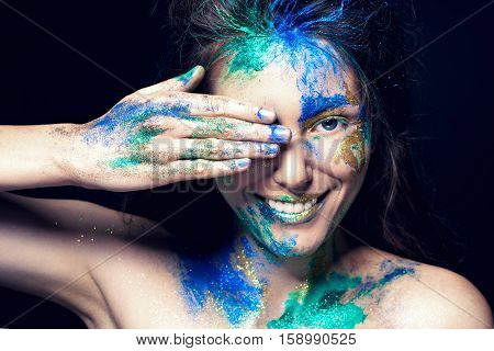 Beautiful face with colored paint on a black background. Beautiful girl. Beautiful young woman. Girl smiling. Colorful makeup. Fashionable woman. Toned image.