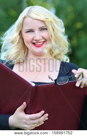 Portrait of happy business woman with open leather folder in front of green foliage