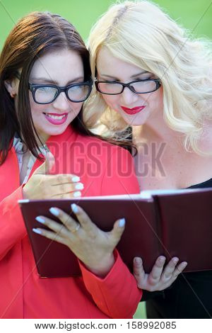 Happy blonde and brunette looking into open leather folder in front of green grass