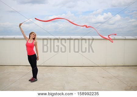 Beautiful blonde with red curly ribbon standing on the roof of a multistory building against the cloudy sky
